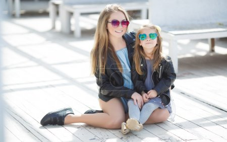Urban portrait of happy mother with little daughter