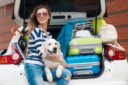 Woman with dog by car full of suitcases.