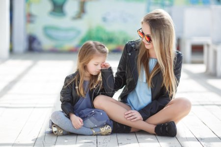 Photo for Beautiful woman in red mirrored glasses in the shape of hearts, blonde with long blond hair in a black leather jacket, spending time outdoors in the spring with his blond daughter, a girl of four years old, wearing a black leather jacket - Royalty Free Image