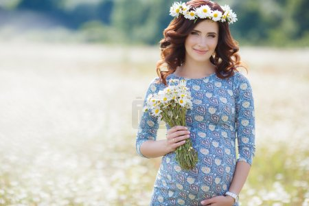 Photo for Happy pregnant brunette woman, in a blue dress with a bouquet of white daisies on his head wears a wreath of flowers white Daisy,walking in the summer field of blooming white daisies on a background of mountains and green trees - Royalty Free Image