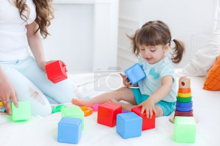 Photo for Beautiful young mother,with long blonde curly hair ,playing with his little daughter in a logical educational games,pyramid and collect the colored blocks,the daughter is a brunette girl with two ponytails on her head - Royalty Free Image