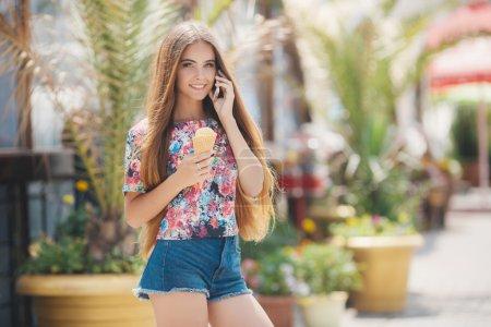 Photo pour Portrait d'été d'une très belle jeune femme aux yeux gris et aux longs cheveux raides bruns, un joli sourire, portant des bijoux, un short bleu et une chemise colorée, la main droite tient un cône de crème glacée, lit le message sur le téléphone portable en été Park - image libre de droit