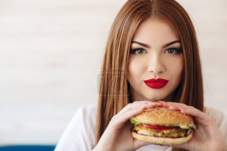 Photo for Beautiful woman with red long straight hair, bright make-up, brown eyes, red lipstick, long eyelashes, pink nail polish in the hands holding a large hamburger, sitting at a table in a cafe, dinner alone - Royalty Free Image