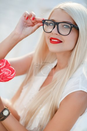 Young sexy blonde woman with heart shaped lollipop and sunglasses. Outdoor.