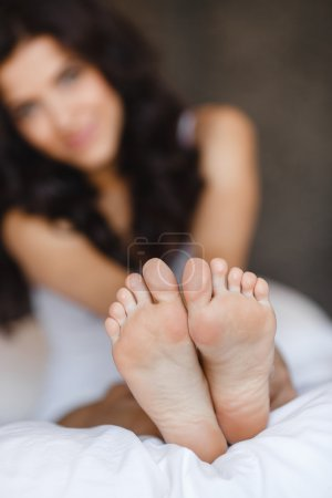 Beautiful feet of a young woman lying in bed close up.
