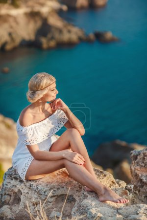 Young beautiful woman sunbathing on rock on tropical beach.