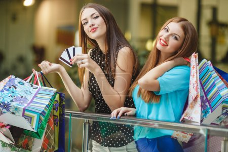 Two women make purchases with credit cards at the mall