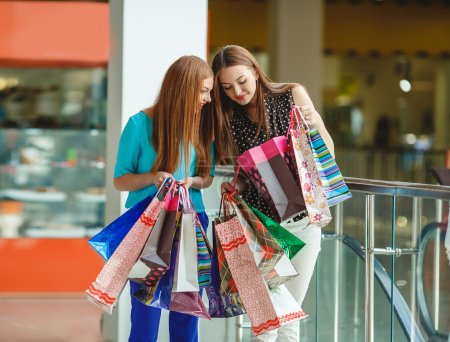 Two young women shop in a big supermarket.