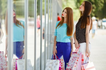 Two cute women view showcases the supermarket.