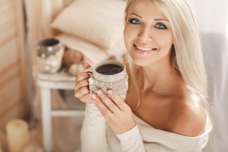 Young woman drinking coffee at home in his room.