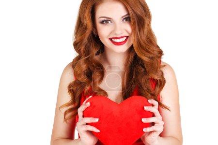 Photo pour Belle jeune femme aux longs cheveux bruns, maquillage lumineux, yeux bruns, et une robe rouge avec un grand cœur rouge dans les mains symbole d'amour sur un fond blanc . - image libre de droit