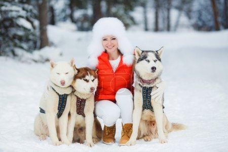 Portrait of a beautiful woman with Siberian huskies - Husky.