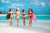 Čtyři štíhlé ženy v bikinách s životnost v blízkosti oceánu