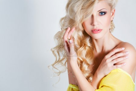 Photo for Young beautiful woman - blonde, with chic long curly hair, blue eyes, beautiful make-up and nail polish, wears a ring on his finger and his ears, beautiful earrings, yellow sleeveless dress, isolated on light gray background. - Royalty Free Image