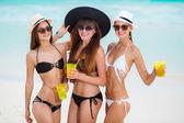 Three girls in hats drinking juice near the sea