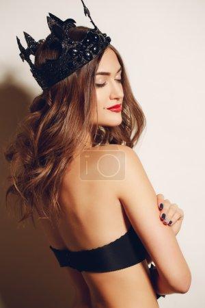 Photo pour La belle jeune femme, la brune aux longs cheveux bouclés et aux yeux marron, une belle tache de naissance près d'une bouche, sur la tête est habillée d'une couronne noire, sur un cou porte un collier, le bracelet sur une main, dans un soutien-gorge noir est habillé . - image libre de droit