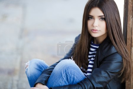 Portrait of a beautiful young woman sitting on the sidewalk.