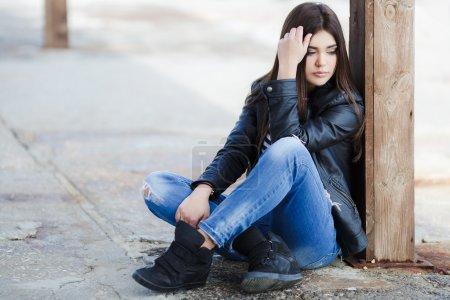 Portrait d'une belle jeune femme assise sur le trottoir