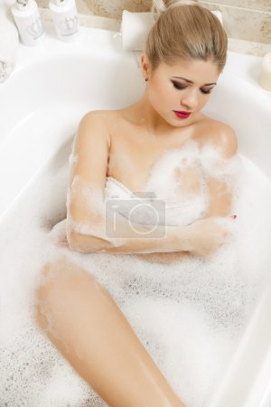 Beautiful blonde takes a bath.