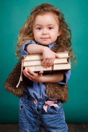 Photo pour Portrait studio d'une jolie petite fille aux longs cheveux bouclés et aux yeux marron avec des livres à la main, vêtue d'une chemise bleue, d'un gilet marron et d'un jean bleu, isolée sur fond bleu . - image libre de droit