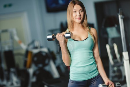 Portrait of a beautiful young sporty woman with dumbbells in her hands.