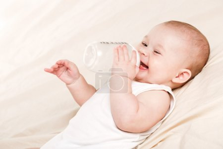 Cute baby with a bottle of milk on a beige blanket