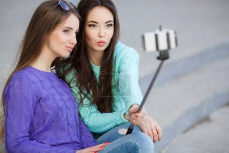 Two young attractive women are photographed with a smartphone in the streets.