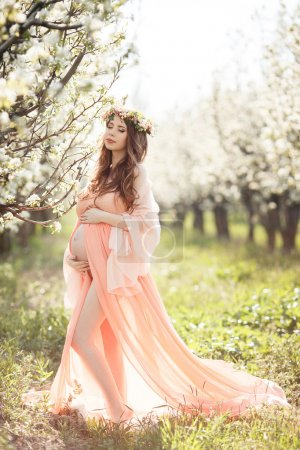 Beautiful pregnant woman in a flowery spring garden.