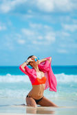 Attractive young woman with red pareo for the beach