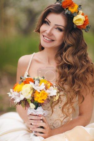 Photo pour Une très belle femme en robe de mariée blanche, avec de longs cheveux bouclés, brune, yeux gris-vert, beau sourire et beau maquillage dans les mains d'un bouquet de mariage, sur sa tête une belle couronne de roses, posant dans le parc au printemps . - image libre de droit
