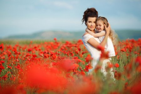 Mother with her little daughter in her arms in a field of blooming poppies.