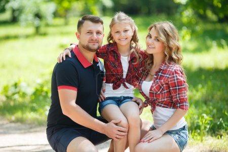 Photo pour Happy young family spending time outdoor on a summer day. family in the park together on a sunny day. Parents and girl look happy and smile. Happiness and harmony in family life. Family fun outside. - image libre de droit