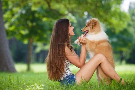 Young beautiful woman playing in a green park with a small puppy collie