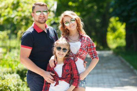 Photo pour Young happy family of three having fun together outdoor. Pretty little daughter. Parents and girl look happy and smile. Happiness and harmony in family life. Family fun outside. - image libre de droit