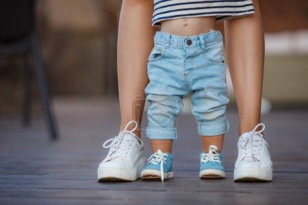 Photo pour Maman en baskets blanches avec un jeune fils, vêtue de pantalons bleus et de chaussures bleues, une chaude journée d'été et apprendre à marcher dans la rue, les premiers pas, la mère entretient son fils . - image libre de droit