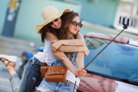 Summer selfie two beautiful girlfriends near car
