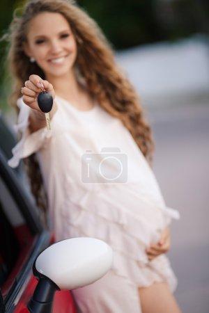 Photo pour Enceinte jeune belle femme avec de longs cheveux sains tenant les clés de voiture debout près de car.Pregnant souriant jolie femme debout près de la voiture - image libre de droit