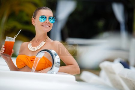 Girl in pool with a glass of red cocktail