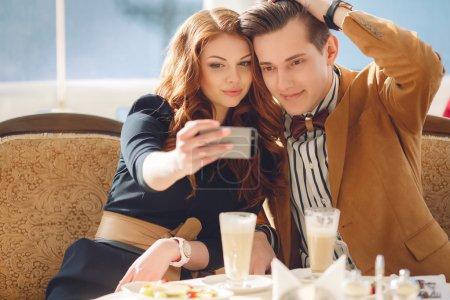 Photo pour Un bel homme, une belle brune aux yeux marron, costume marron clair et noeud papillon et jeune femme aux cheveux roux aux yeux marron, portant une robe noire, passent du temps ensemble autour d'une tasse de café en plein air en été, regardant des photos sur mobile pho - image libre de droit