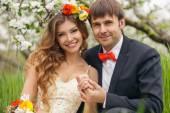 Portrait newlyweds in the lush spring garden