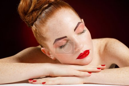Photo for Portrait of a Girl with bright makeup, beautiful red hair pulled back in her hair, tired , dropped his head in his hands and closed his eyes, a sexy portrait of sleeping woman with creative makeup in Studio - Royalty Free Image