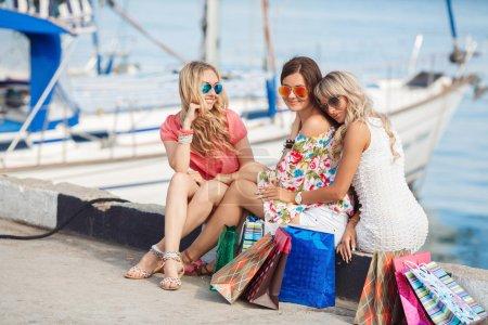 Photo pour Bonnes jeunes femmes, deux blondes et une brune aux longs cheveux bouclés, lunettes foncées, vêtues de vêtements lumineux, passent leurs vacances à la station en été, marchent le long du front de mer près du yacht club et profitent de la beauté de l'océan bleu . - image libre de droit