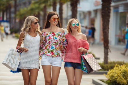Photo pour Trois jeunes femmes, deux blondes et une brune, vêtues de chemises et de shorts d'été, de lunettes de soleil, avec des sacs en papier lumineux passent leurs vacances à faire du shopping et à marcher dans les supermarchés vers les petits magasins de la station balnéaire, le concept de tourisme . - image libre de droit