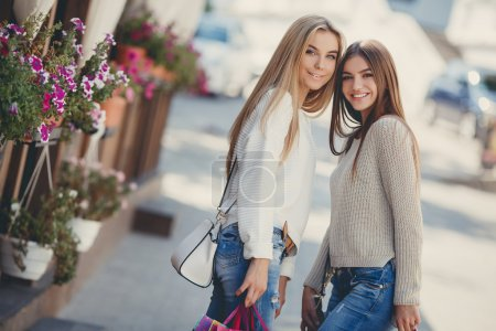 Photo for Two young beautiful women,good friends,a blonde and a brunette, with long straight hair,dressed in blue jeans and a light knitted sweaters are returned from the supermarket with colored bags post fashion shopping,posing on a city street - Royalty Free Image