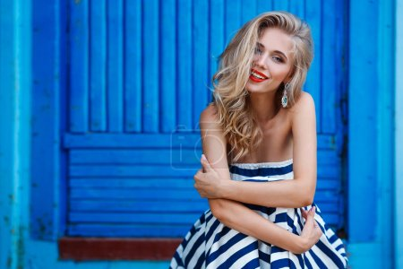 Photo for Fashion portrait. Smiling blonde woman in fashionable look. Sea style. On blue background. Style and hot girl outdoor. - Royalty Free Image