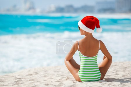 Girl sitting on the beach in a cap of Santa Claus