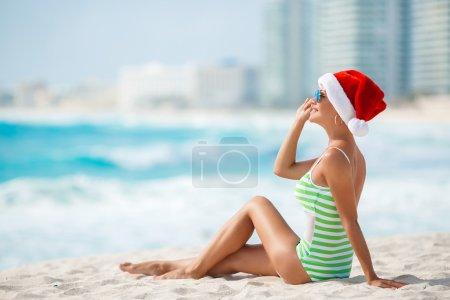 Photo for Young woman in santa hat sitting on beach. Christmas vacation. Christmas beach vacation travel woman wearing Santa hat and bikini enjoying christmas on tropical beach. woman in santa hat and bikini - Royalty Free Image