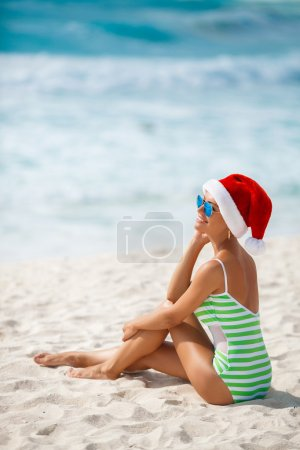 Photo for Young woman in santa hat sitting on beach. Christmas vacation. Christmas beach vacation travel woman wearing Santa hat and bikini enjoying christmas on tropical beach. woman in santa hat and bikini - Royalty Free Image