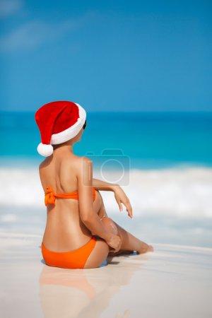 Photo for Young woman in santa hat on tropical beach. Christmas vacation. Christmas beach vacation travel woman wearing Santa hat and bikini enjoying christmas on tropical beach. woman in santa hat and bikini - Royalty Free Image