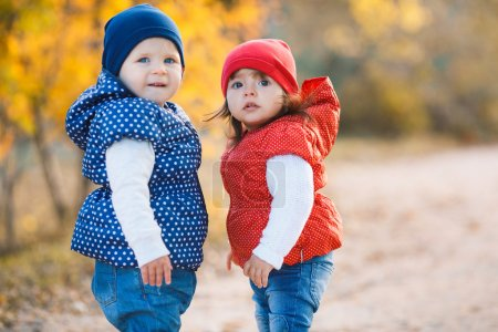 Photo for Two little girls happy friends playing together in the alley in the park on a background of yellow trees and bushes, dressed in jackets and knitted hats of red and blue on the legs wearing white shoes - Royalty Free Image